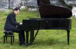 Il pianista fuori posto. Appuntamento con Paolo Zanarella e la sua musica in Viale Europa a Roma con lo sfondo della basilica di San Pietro e Paolo